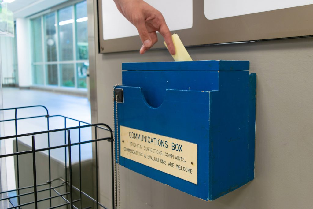 A hand places paper into a suggestion box